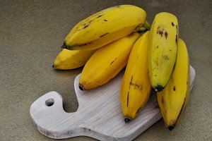 yellow bananas on cutting board