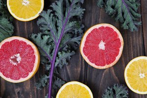 Citrus and Kale on a Wood Background