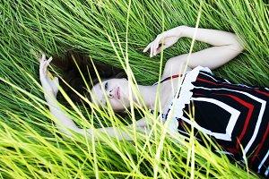 woman lying in green fresh grass