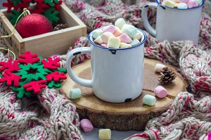 Homemade hot chocolate topped with marshmallow in enamel mug, warm scarf on background, horizontal
