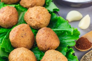 Chickpea falafel balls with vegetables and sauce on black plate, vertical