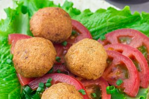 Chickpea falafel balls with vegetables and sauce, roll sandwich preparation, vertical