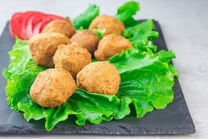 Chickpea falafel balls on slate board with vegetables and sauce, horizontal, copy space