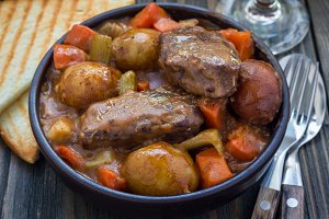 Hearty beef stew with carrot, celery, shallot and potato, horizontal, closeup
