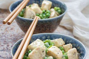 Fried chicken with green peas in cream sauce, served with rice, vertical