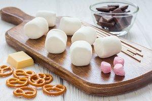 Ingredients for homemade christmas sweetness: marshmallow, chocolate, pretzel, wooden sticks, horizontal