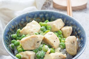 Fried chicken with green peas in cream sauce, served with rice, vertical, copy space
