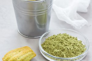 Homemade matcha green tea madeleines on the table and in metal bucket, vertical