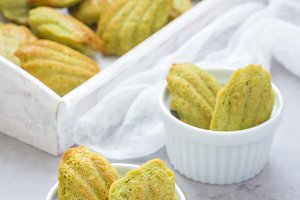 Homemade matcha green tea madeleines on the table and in wooden tray, vertical