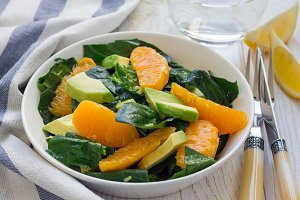Healthy spinach, avocado and orange salad with ginger-vinegar dressing, horizontal