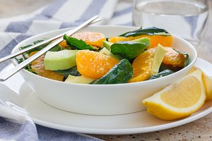 Asian style healthy spinach, avocado and orange salad with ginger-vinegar dressing, horizontal