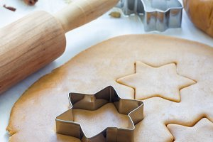 Making gingerbread cookies. Dough, metal cutter and rolling pen on wooden table, spices on background, vertical