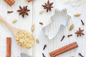Christmas background with different spices, flour and cookie cutters on white wooden table, vertical, top view