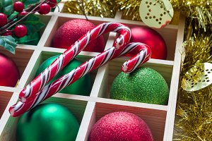 Preparation for Christmas: festive balls and candy cane in wooden box, horizontal