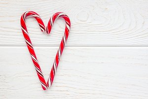 Crossed peppermint candy canes on white wooden background, copy space, top view