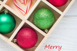 Preparation for Christmas: festive balls and candy cane in wooden box on white wooden table, square format, text