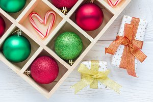 Preparation for Christmas: festive balls and candy cane in wooden box, gifts on white wooden table, horizontal
