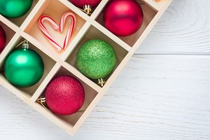 Preparation for Christmas: festive balls and candy cane in wooden box on white wooden table, horizontal, copy space