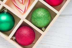 Preparation for Christmas: festive balls and candy cane in wooden box on white wooden table, square format, copy space