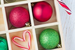 Preparation for Christmas: festive balls and candy cane in wooden box on white wooden table, vertical