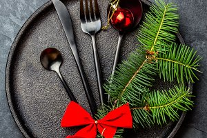 Black cutlery set, Christmas decoration on iron plate, slate background