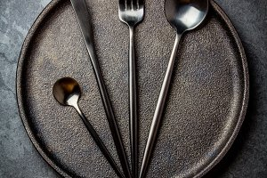 Cutlery set on plate. black table setting. Top view