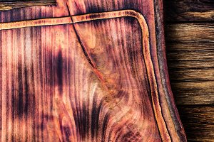 Vintage rustic cutting board on old wooden background. Top view