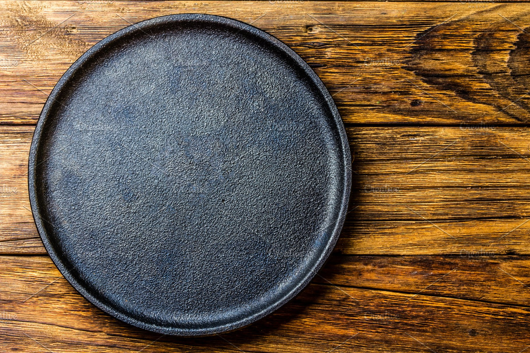 Empty Rustic Black Cast Iron Plate Over Old Wooden Background