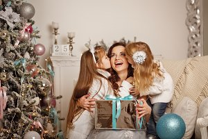 Daughters kissing mother. Christmas
