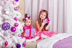 Two girls are happy Christmas gifts