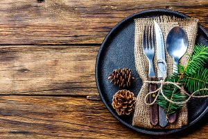 Vintage cutlery set, Christmas decoration on iron plate, wooden background
