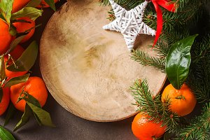 Ripe tangerines on a green branch and tree, Christmas toys, balls, star dish. Gray background. Space for text. Top view