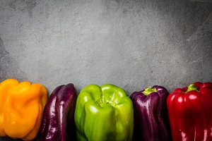 Many colored bell peppers on grey slate background