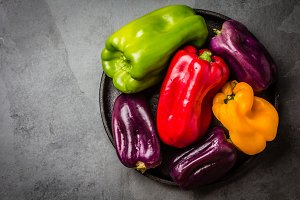 Many colored bell peppers on black plate, grey slate background
