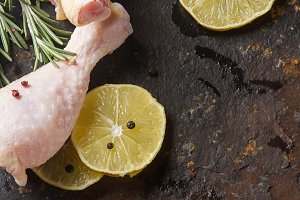 Chicken legs with rosemary, pepper and lemon. Dark background. Lunch on the grill. Space for text. Top view