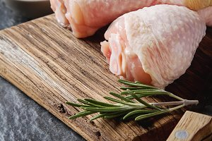 Chicken legs with rosemary and spices. Dark background. Lunch on the grill. Space for text.