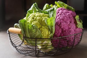 Rainbow of organic cauliflower in a metal basket with a dark cloth. Grey table.