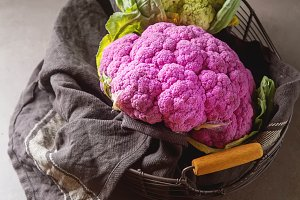 Rainbow of organic cauliflower in a metal basket with a dark cloth. Grey table. Top view