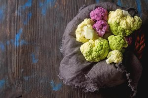 Rainbow of organic cauliflower and Romanesco broccoli on wooden table. Top view