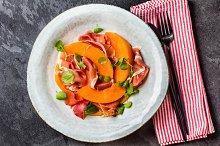 Ham jamon, melon and arugula salad on grey plate