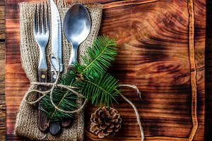 Vintage cutlery set, Christmas decoration on wooden cutting board