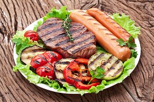 Grilled steak, sausages, vegetables