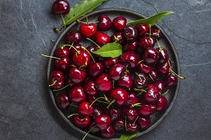 Fresh cherry on black plate, slate background. Top view