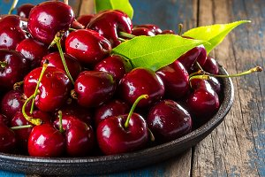 Fresh cherry on black plate, wooden background
