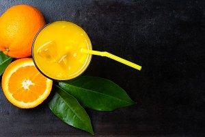 Fresh orange juice, fruits with leaves on black background