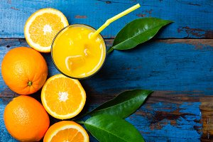 Fresh orange juice, fruits with leaves on wooden blue background