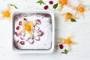 Chocolate cake with berries strawberry physalis and mint, white background