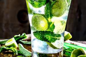 Mojito cocktail with lime and mint on wooden rustic background
