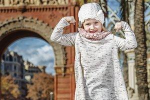 child near Arc de Triomf in Barcelona, Spain showing strength