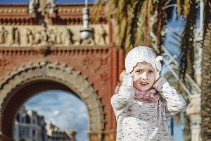 girl near Arc de Triomf in Barcelona, Spain holding her hat